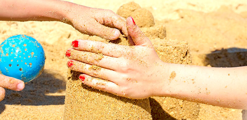 Close Up Of Hands Building Sand Castle