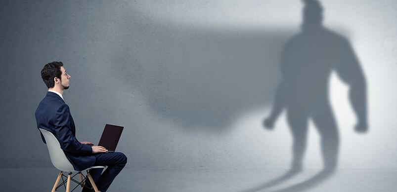 Businessman Looking At Superhero Shadow