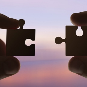 Two Hands Holding Parts Of Puzzle