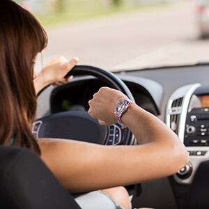 Woman Driving Car Looking At Watch