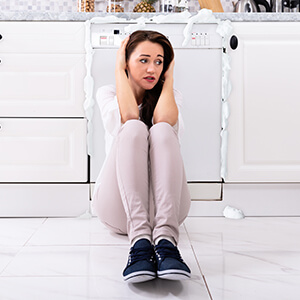 Woman Sat By Dishwasher Covering Ears