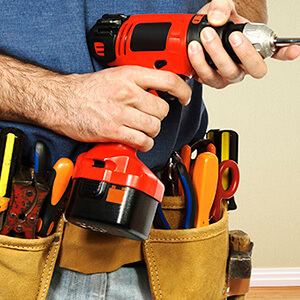 Man Wearing Toolbelt Holding Drill