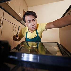 Man Looking Into Oven With Screwdriver