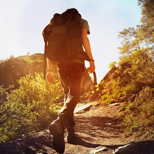 Man Hiking Uphill At Sunset