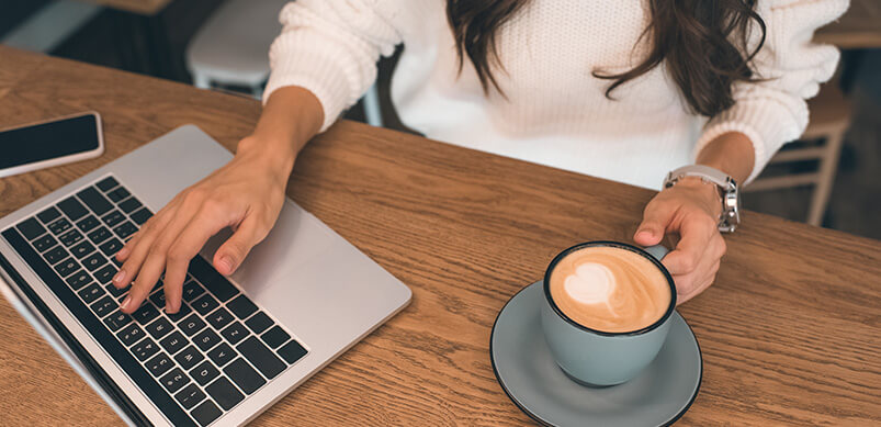 Woman With Laptop And Coffee Cup On Desk