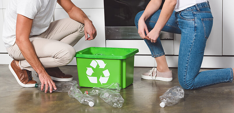Couple Recycling Plastic At Home