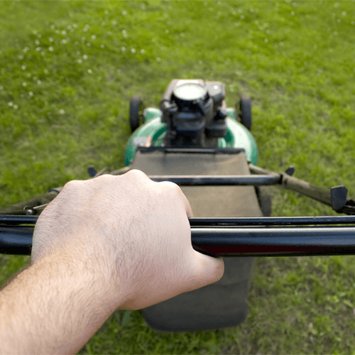 Close Up Of Hands Pushing Lawnmower