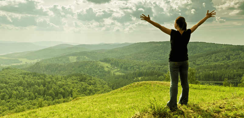 Woman With Arms Reaching Up On Hill