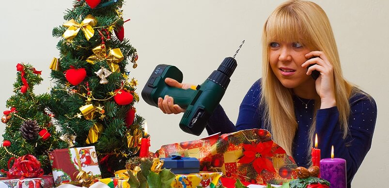 Woman on phone with Christmas tree and drill
