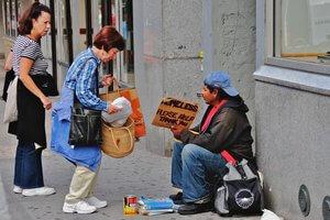 Woman giving food to homeless man