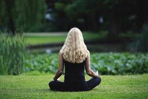 Gril meditating on grass