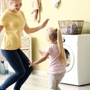 Woman And Daughter Dancing In Home