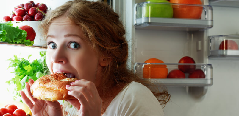 Woman Eating Food from Fridge Looking Guilty