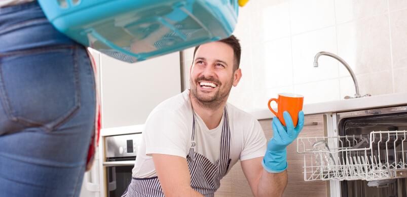 Man Smiling Next to Dishwasher