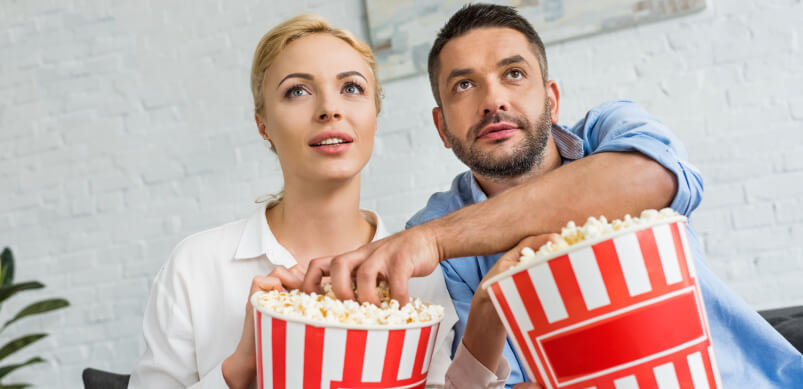 Couple Glued To TV With Popcorn