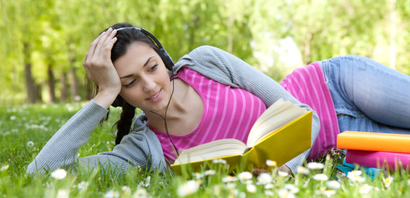 Woman Reading Book Sitting In Flowers