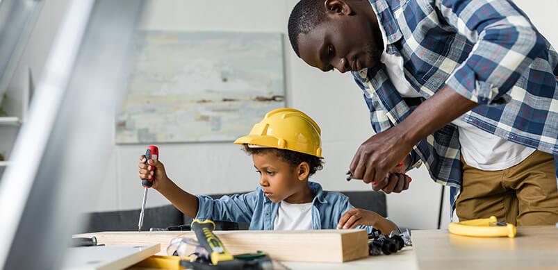 Man Teaching Son To Fix