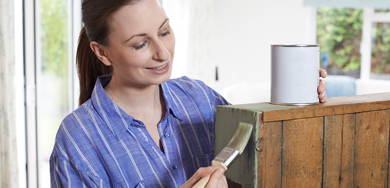 Woman Painting Wooden Cabinet