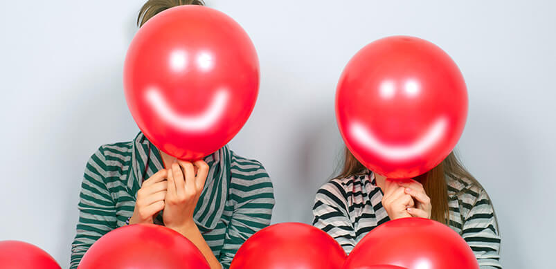 Kids Holding Balloons With Smiley Faces