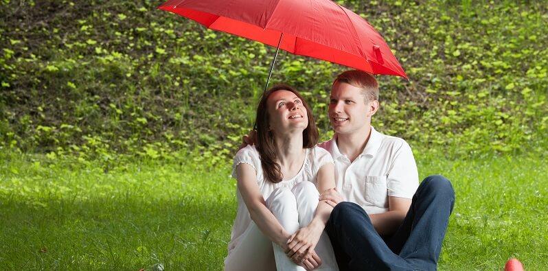 Couple Having Picnic With Umbrella