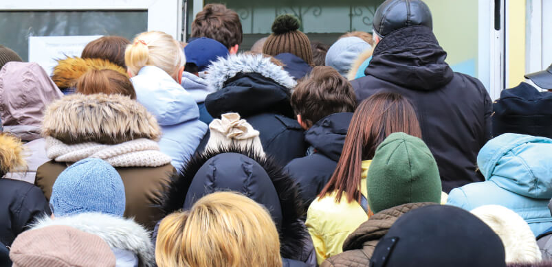 Crowd Of People Queuing Outside Shop