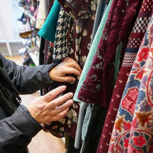 Woman Looking Through Clothes In Second Hand Shop