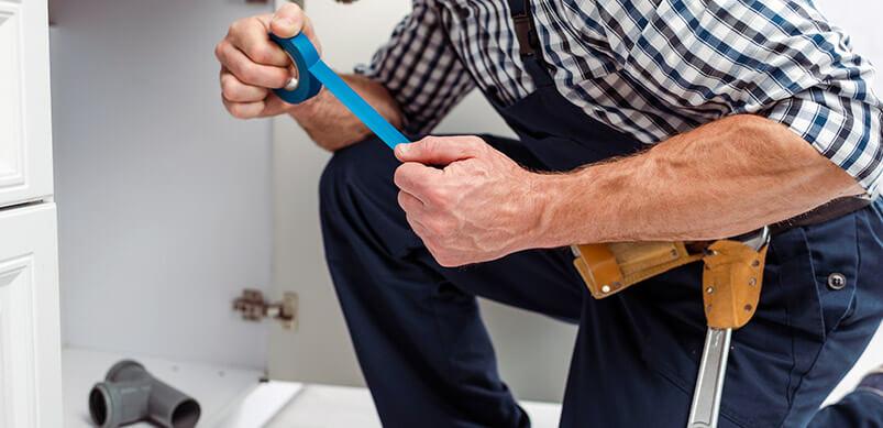 Man Taping Sink Pipe