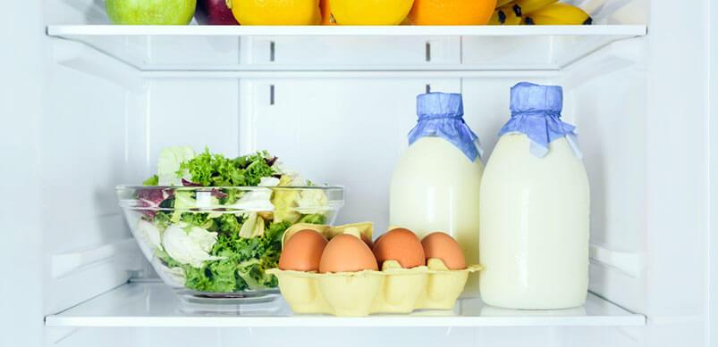 Eggs and Milk on Fridge Shelf