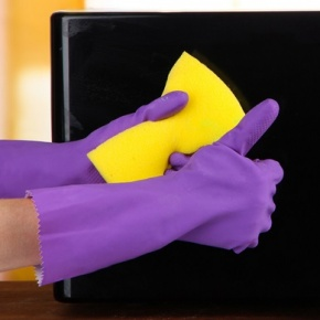 Hand with sponge cleaning microwave